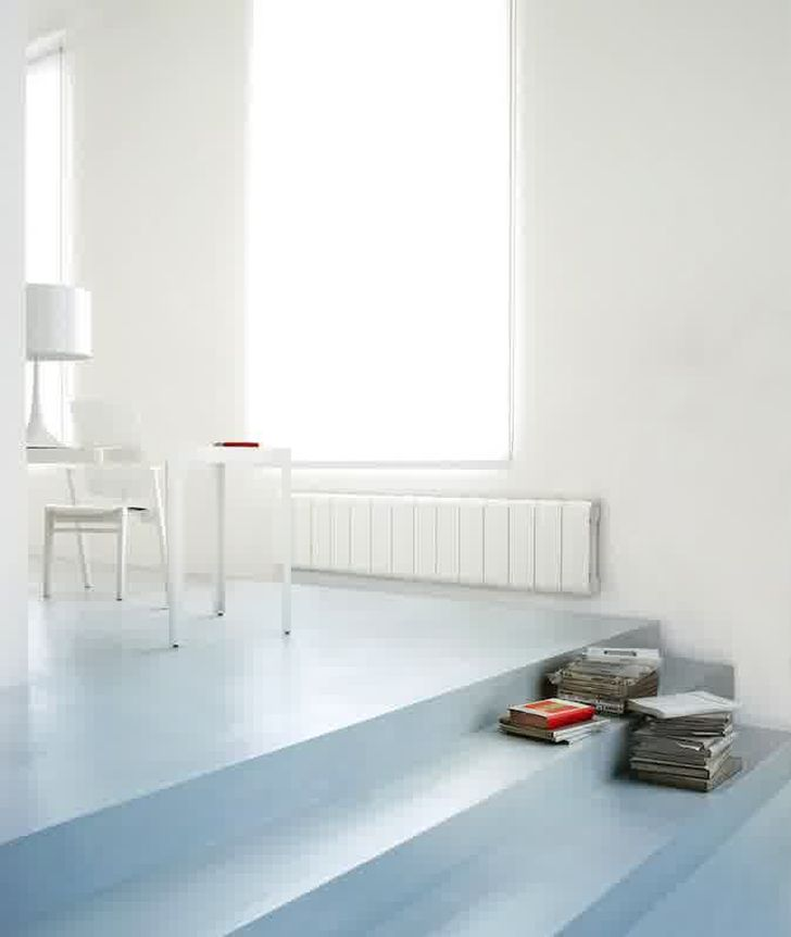 Aluminium Radiators in Agora Collection Long White Radiator in the Family Room with Stacks of Books and White Wooden Table and Chair