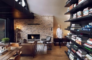attic-apartment-with-custom-furniture-apartment-living-room-wooden-table-and-dark-bookshelf-brown-sofa-brick-fireplace