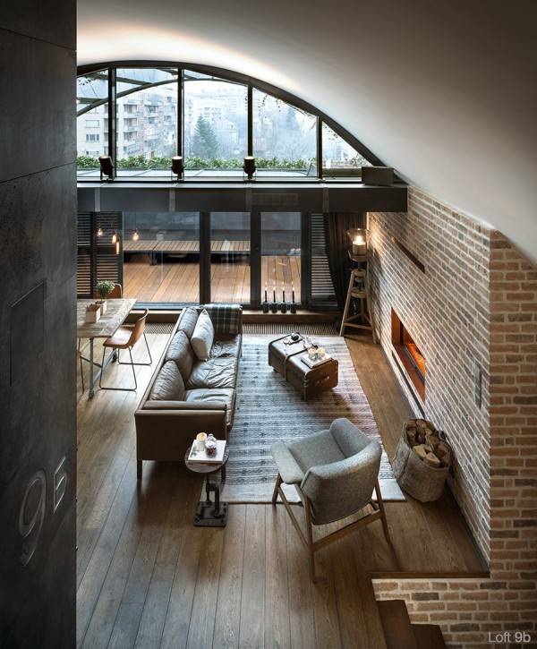 attic-apartment-with-custom-furniture-family-room-with-brick-fireplace-glass-wall-flooring-lamp-custom-paneling-brown-sofa-suitcase-table