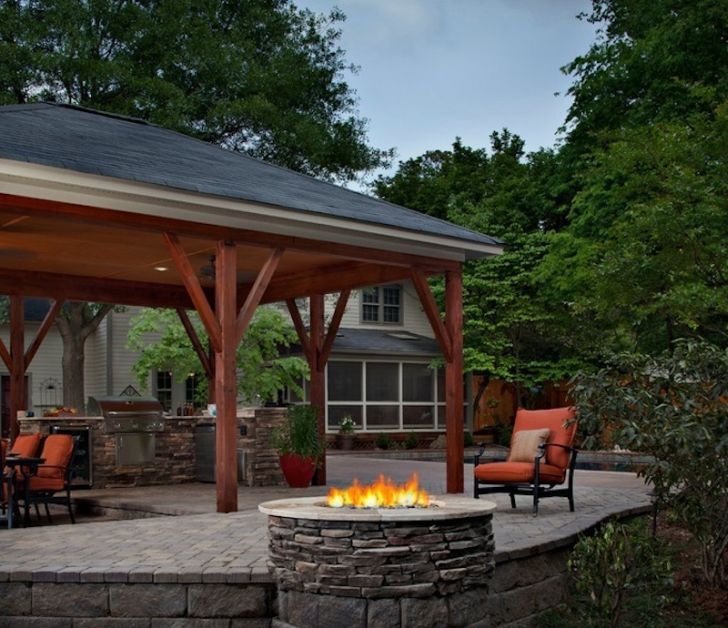 smart patio ideas outdoor-kitchen-with-red-chair-patio-and-stone-fireplace