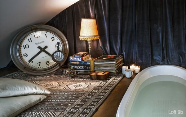 attic-apartment-with-custom-furniture-sunken-bathtub-in-second-floor-bedroom-stacks-of-books-table-lamp