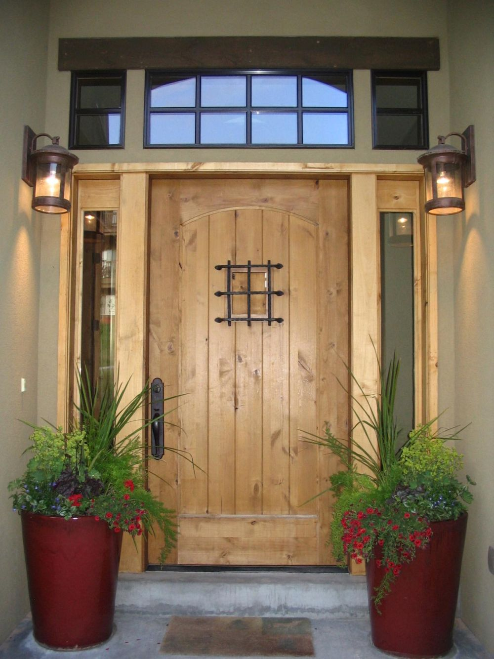 front door decoration with two wall mount outdoo lighting and two red flower vases