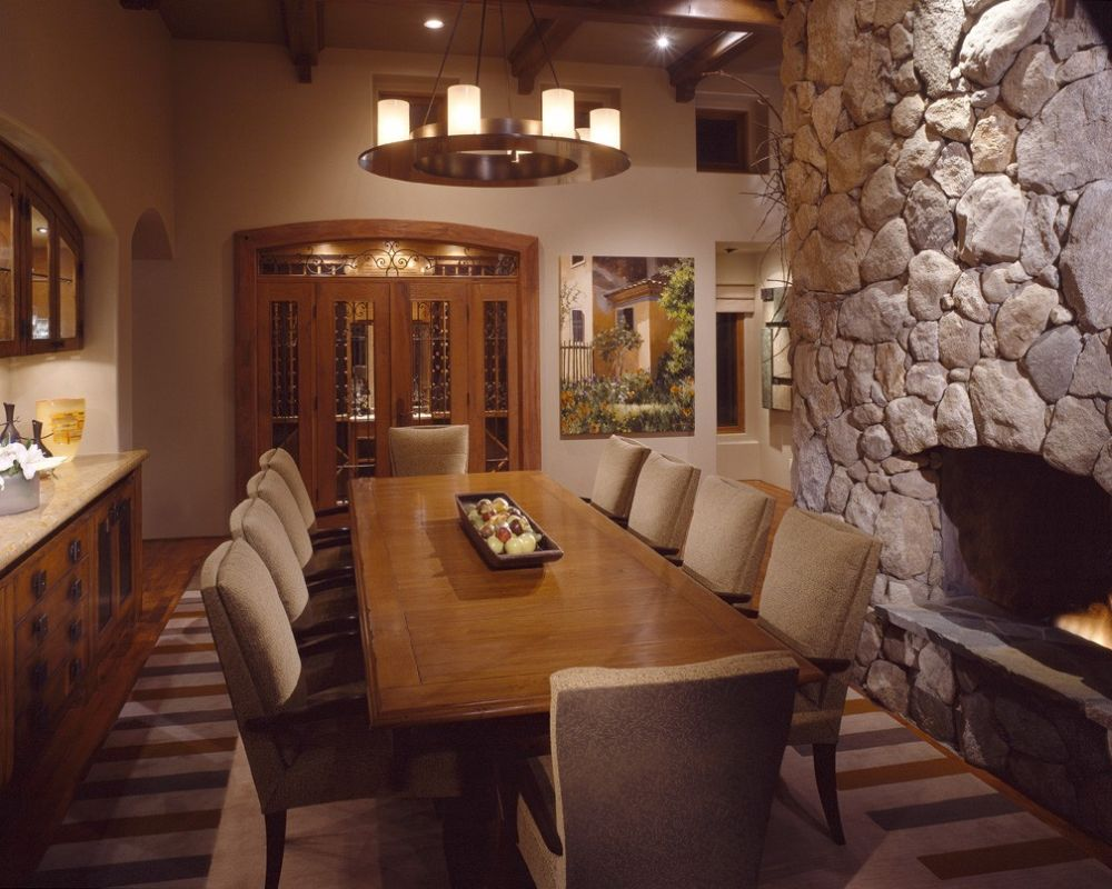 long rectangular wooden dining table with beige upholstered chairs and big stone fireplace