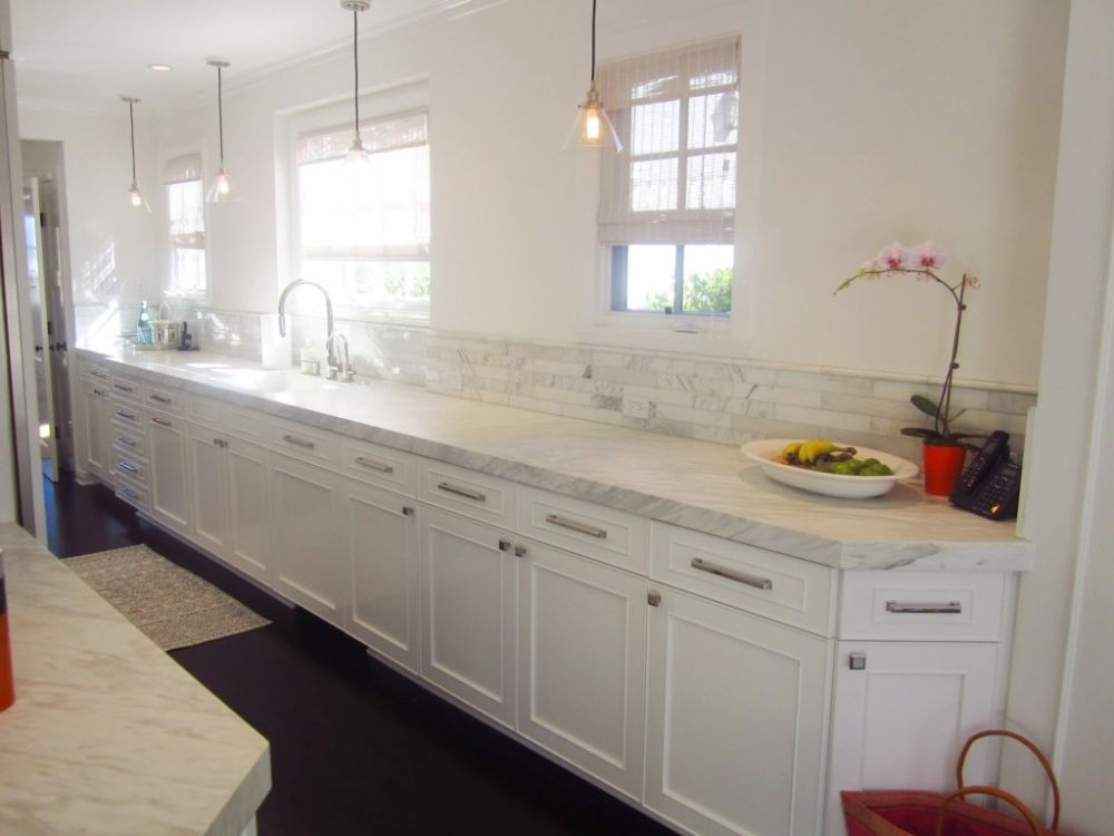 sleek white themed kitchen design with long white cabinetry and cafe pendant lights
