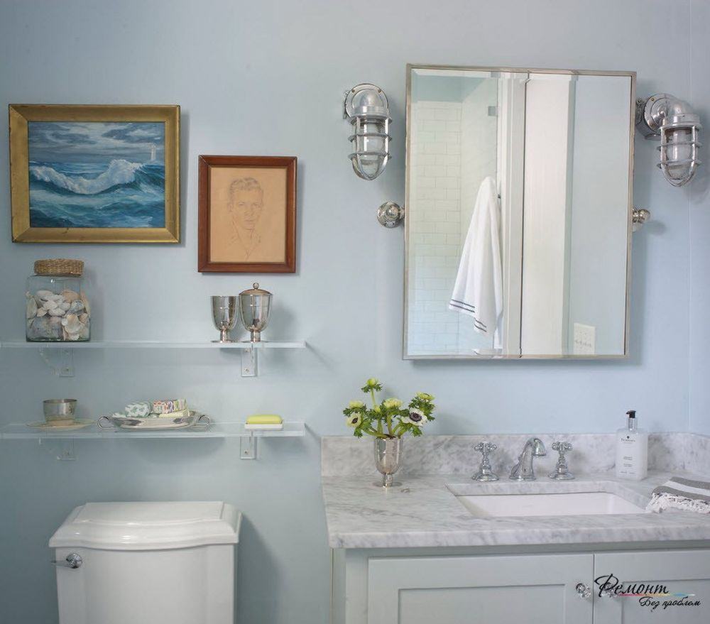 white glass shelves on the light blue wall with framed painting and nautical theme