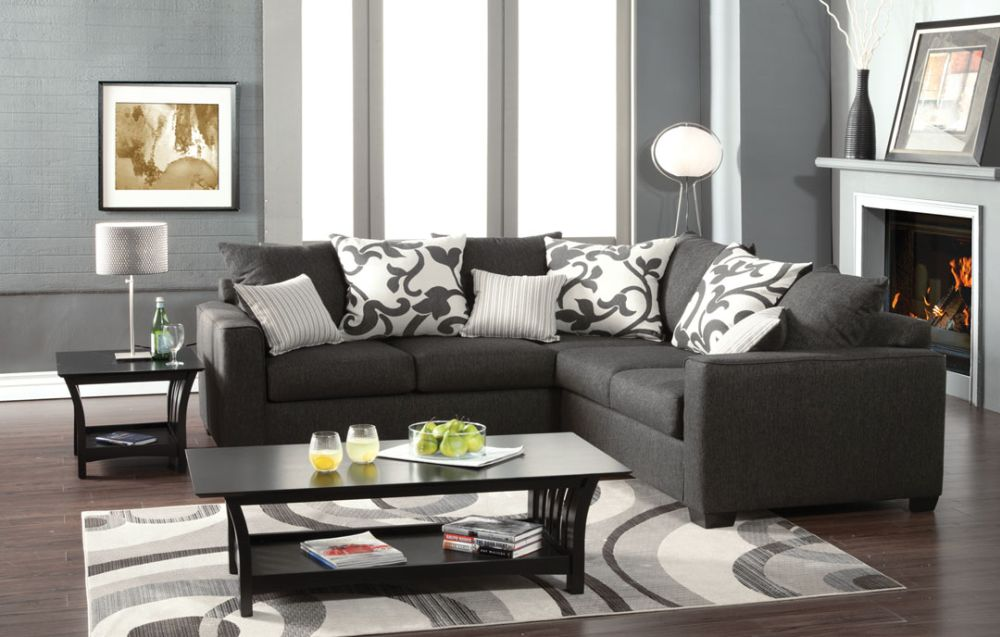 dark gray v-shaped sectional sofa with several white patterned throw pillows stylish sectional sofas that work optimally for small spaces
