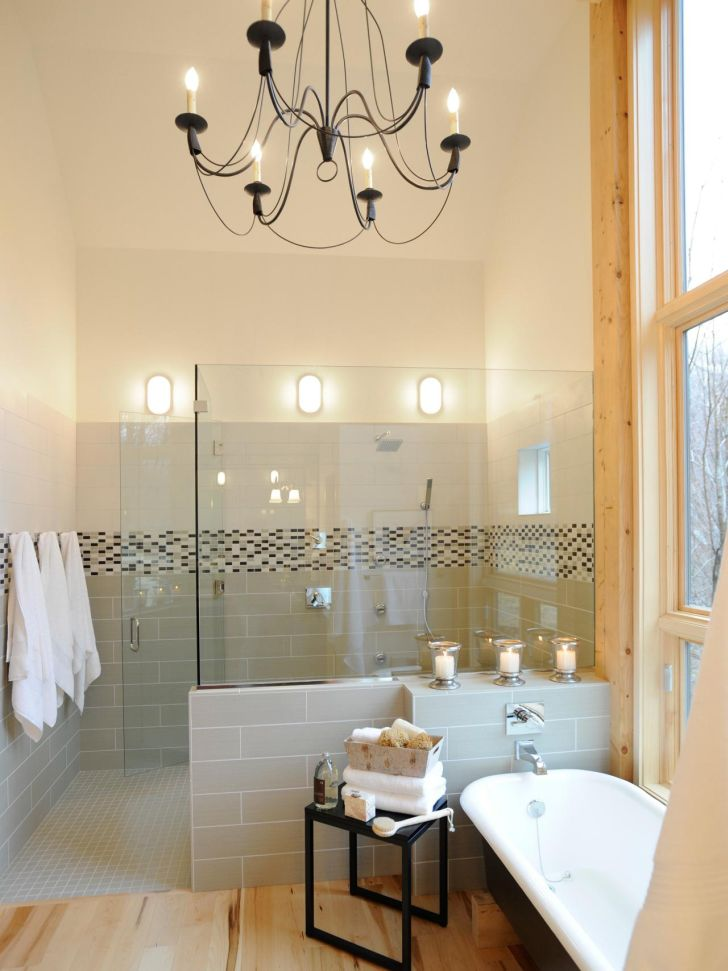 Small Bathroom with Decorative Chandelier Lighting plus Glass Wall Shower and White Bathub