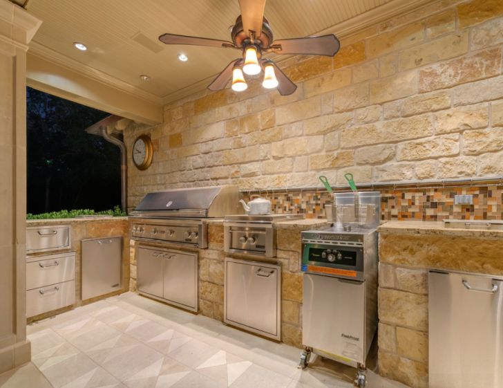 outdoor kitchen design-outdoor-kitchen-lighting-ceiling-fan-white-stone-brick-wall-stainless-storages