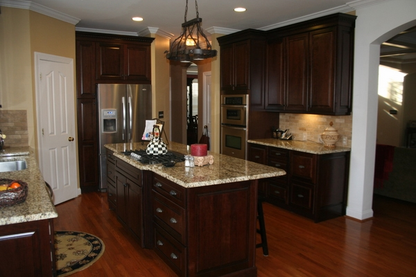 Kitchen Design with Wooden Flooring with Dark Wood Kitchen Cabinets and Giallo Ornamental Granite Countertops