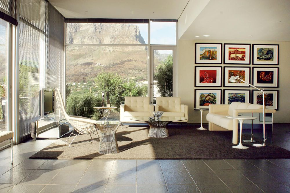 contemporary living room with glass top platner coffee table and beige sofa sets