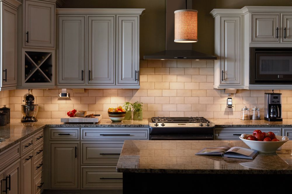 country style kitchen design with over cabinet lighting and rustic kitchen island with a granite top