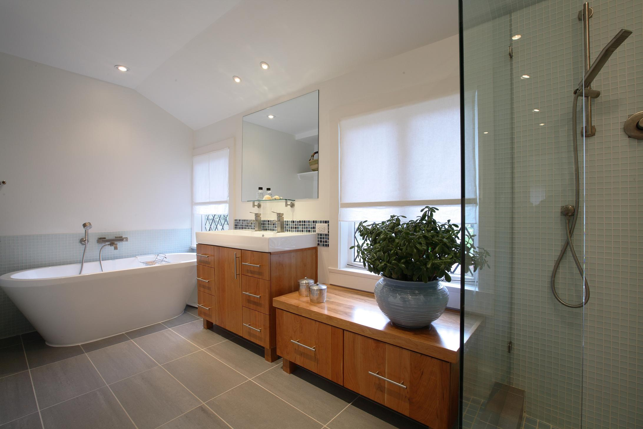 elegant bathroom decoration design with large white bathub and wooden vanity sets plus ceramic sink
