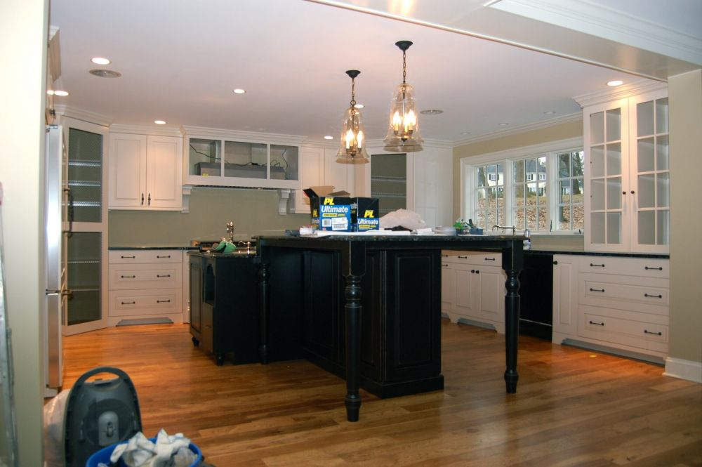 elegant white kitchen island with two classic crystal chandeliers and retro wooden stools