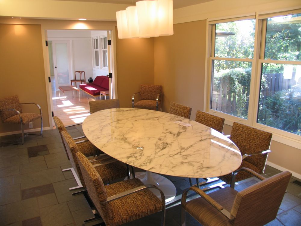 formal modern dining room design with oval marble top and brown microfiber chairs plus dim lights