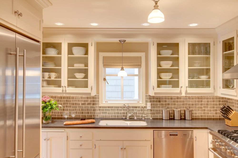 fresh and clean kitchen design with brick backsplash and l-shaped white cabinetry plus over the sink lighting