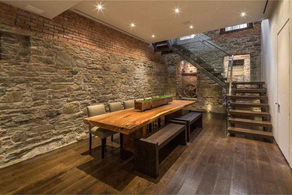 long wooden dining table in the basement with wooden bench and chair
