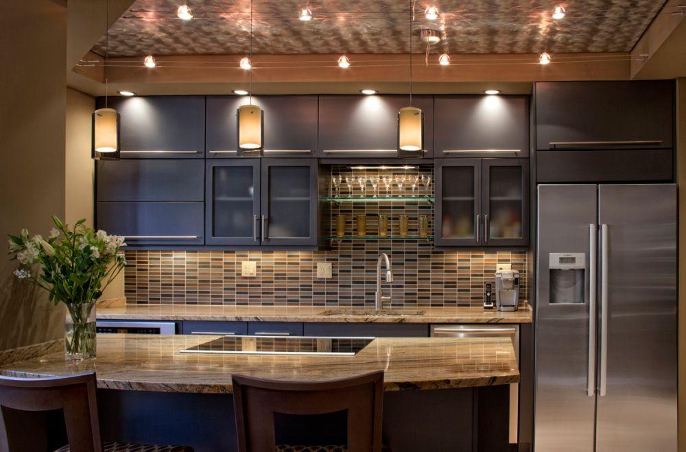 modern kitchen island design with three track pendant lights and black engineered wood storage