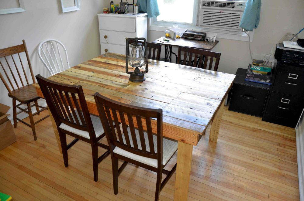 rectangular pallet dining table with old lantern and wooden chairs