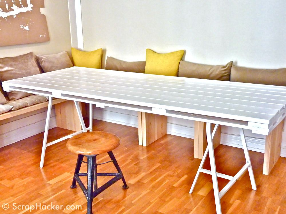 wooden L-shaped bench with comfy pads and white pallet dining table