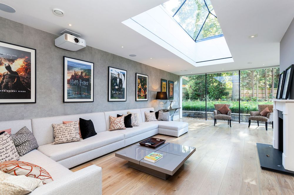 elegant sitting room with long gray sofa with colorfull cushion and artistic ceiling with natural light by beaumont interiors london presenting best interior design with extra long sofa